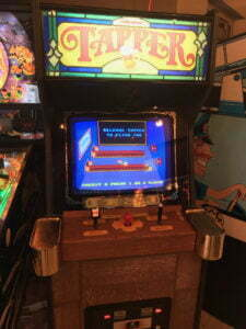 Tapper arcade cabinet with beer tap handle and brass drink holders on the side.